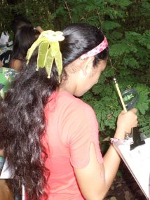 An Abriendo Mentes student examines a plant with her magnifying glass